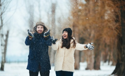 smiling-couple-playing-with-snow-field_1153-1427